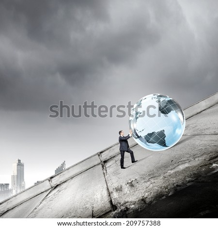 Businessman rolling Earth planet up the hill - stock photo