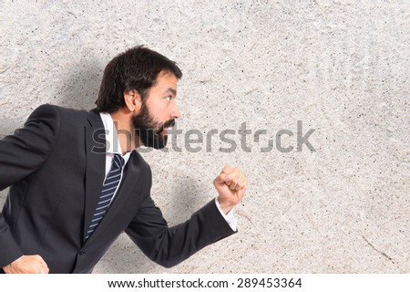 Businessman running fast over textured background - stock photo