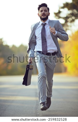 Businessman running in park - stock photo