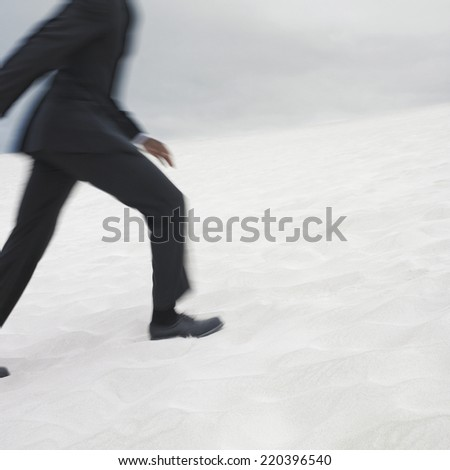 Businessman running in the desert - stock photo