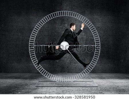 businessman running in wheel in gray concrete room - stock photo