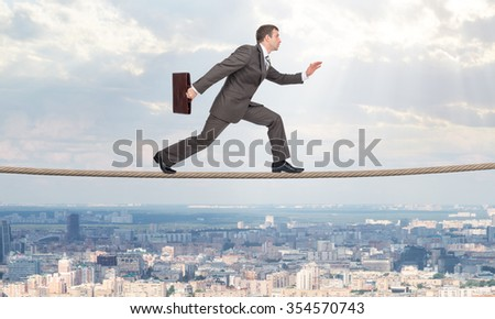 Businessman running on rope above city with closed eyes