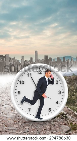 Businessman running on the phone against stony path leading to large city on the horizon - stock photo