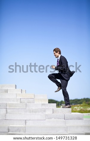 Businessman running up stairs outside. Achieving goals through challenges, showing courage.
