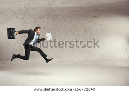 businessman running with some papers in his hand - stock photo
