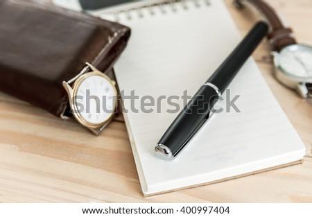 Businessman's accessories, notepaper, pen, wristwatch, wallet - stock photo