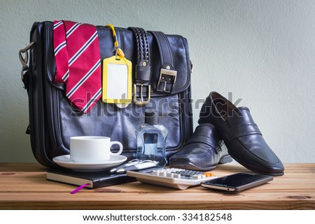 Businessman's accessories with shoes, necktie, black briefcase, and belt on wooden table over grunge background