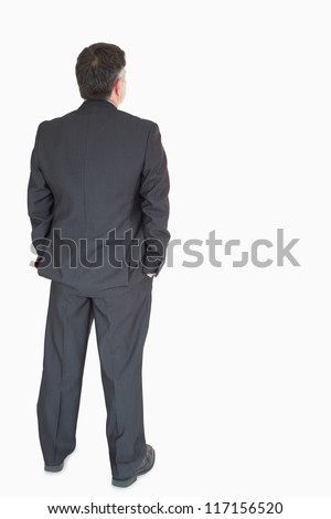 Businessman's back with hands in pockets - stock photo