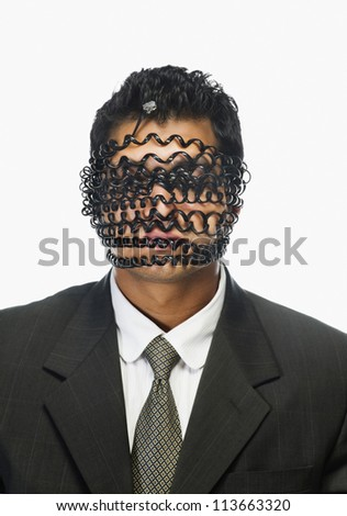 Businessman's face wrapped with telephone cord - stock photo