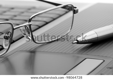 Businessman's glasses and pen on laptop computer - stock photo