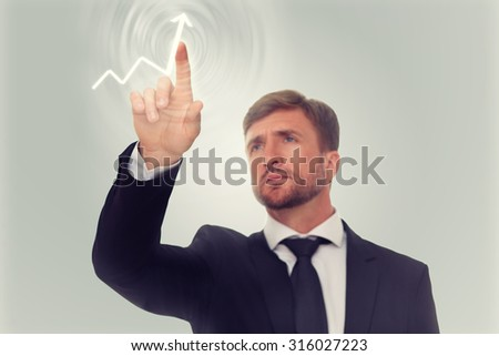 Businessman's hand drawing increasing graph on media screen. Serious man has a desire to see the prosperity of his company.