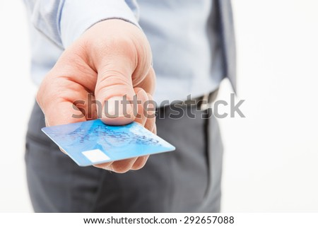 Businessman's hand giving credit card to you, closeup shot - stock photo