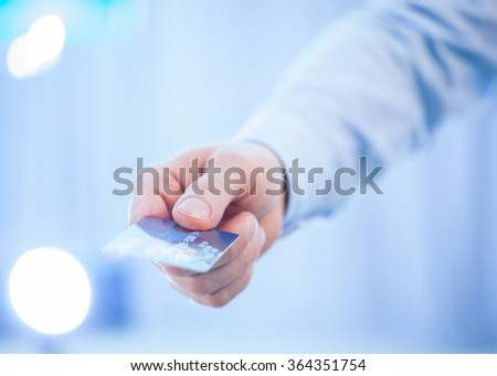 Businessman's hand giving credit card to you, closeup shot