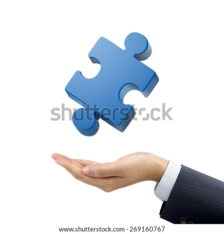 businessman's hand holding jigsaw puzzle piece over white background