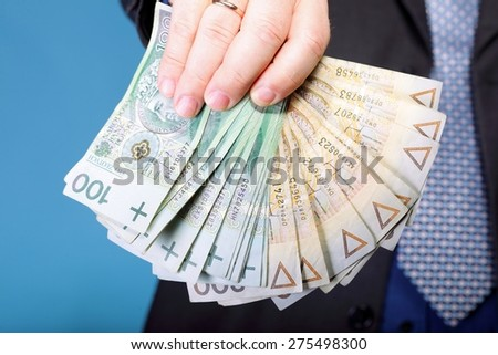 Businessman's hand holding polish money banknote blue background - stock photo