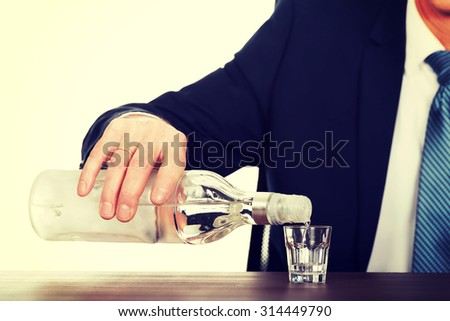 Businessman's hand pouring vodka into a glass. - stock photo