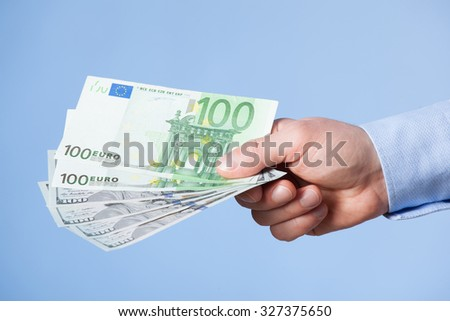 Businessman's hand reaching out euro banknotes, blue background - stock photo