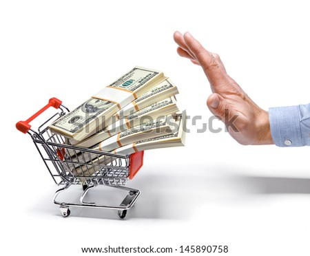 businessman's hand & shopping cart full of stacks of dollar bills / man's hand stops the cart full of money stacks - isolated on white background  - stock photo