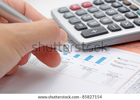 Businessman's hand showing diagram on financial report with pen. - stock photo