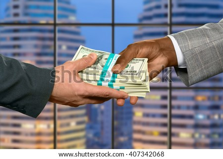 Businessman's hand taking big money. Repaying debt in the city. He gained a significant percent. Good month for a salesman.  - stock photo