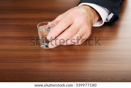 Businessman's hand with a glass of alcohol. - stock photo