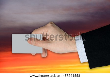 Businessman's Hand with blank credit Card on dramatically Sky