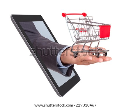 Businessman's hand with shopping cart emerging from digital tablet isolated over white background