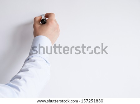Businessman's hand writing something on a white wall - stock photo