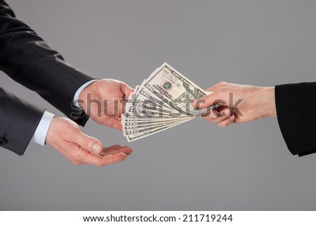 Businessman's hands accepting an offer of money on grey background