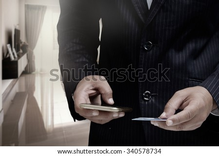 Businessman's hands holding a credit card and using smart phone for online shopping.