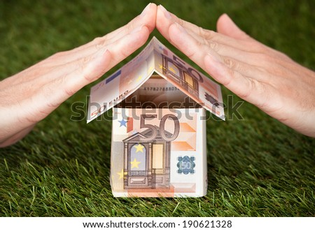 Businessman's hands protecting house made of euro notes on grassy land