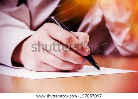 businessman's hands while writing some documents, closeup