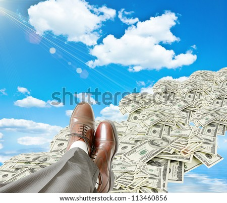 businessman's legs are resting on heap of dollars