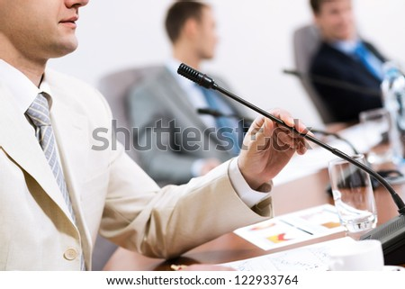 businessman, said into the microphone, in the background colleagues communicate with each other - stock photo
