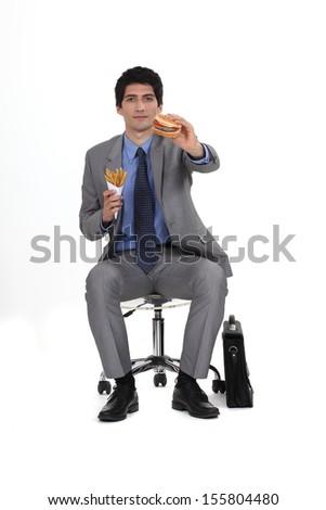 Businessman sat eating burger and fries - stock photo