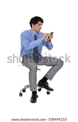 Businessman sat on chair sending SMS - stock photo