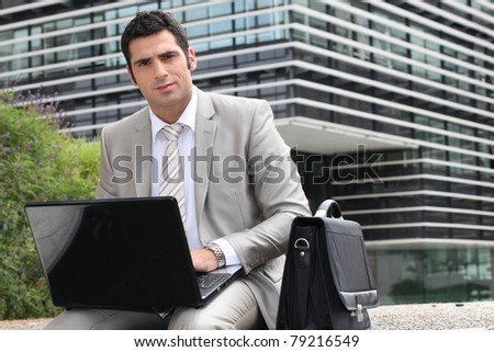Businessman sat outside with laptop computer - stock photo