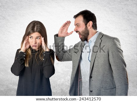 Businessman screaming at his girlfriend over textured background