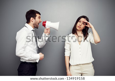 businessman screaming at the fatigued woman. studio shot over dark background - stock photo
