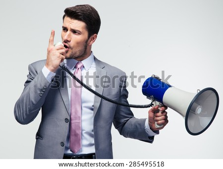 Businessman screaming in megaphone over gray background. Looking away - stock photo