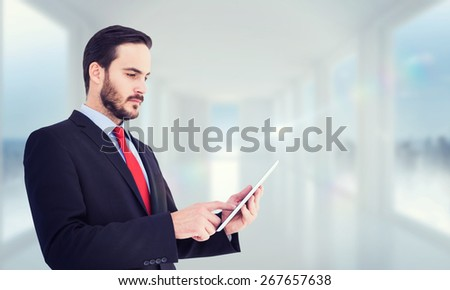 Businessman scrolling on his digital tablet against bright white hall with windows - stock photo