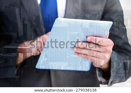 Businessman scrolling on his digital tablet against room with large window looking on city - stock photo