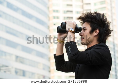 Businessman search stock through binoculars for check and predict trend marketing - stock photo