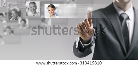 Businessman searching a user profile online and touching a touch screen interface - stock photo