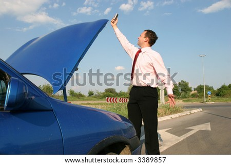 Businessman searching for a mobile network in front of a broken car - stock photo