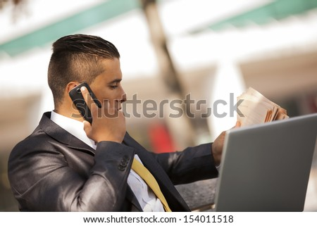 Businessman seated in a bench park, working with his laptop, calling at the cellular and reading his newspaper
