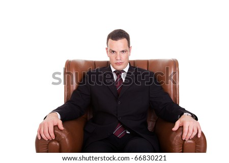 Businessman seated on a chair, isolated on white background. Studio shot. - stock photo