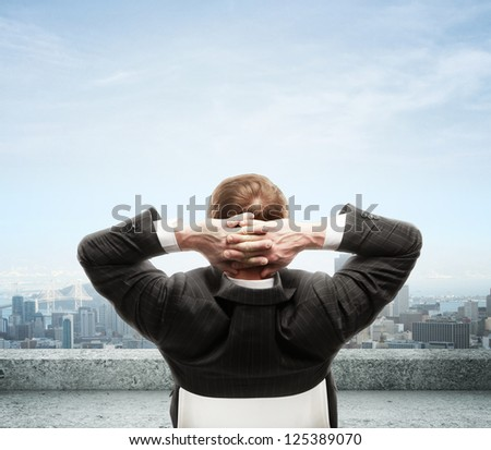 businessman seeting and seeing to city from roof