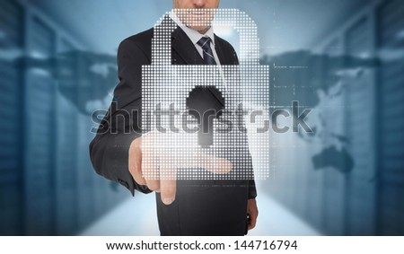 Businessman selecting a digital padlock with a world map on the background - stock photo