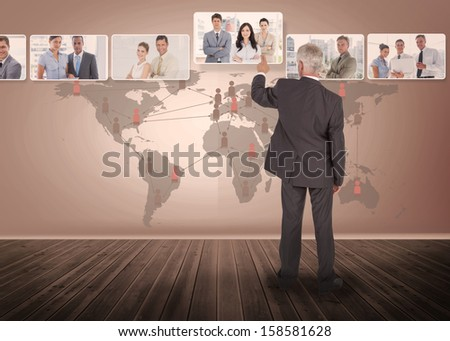 Businessman selecting digital interface showing business people with map on background - stock photo